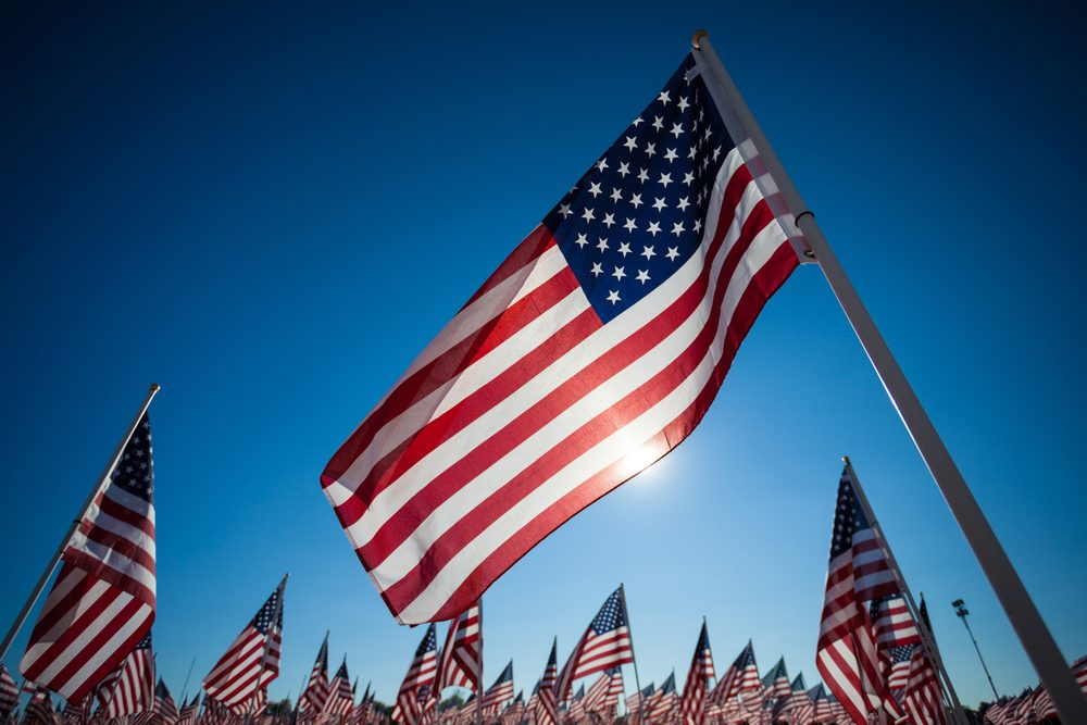 Foreground: American flag backlit by the sun. Background: a grouping of American flags.