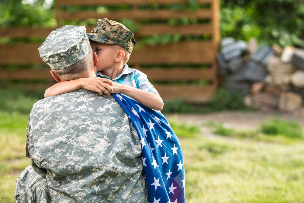 Young boy embracing his military father, American flag draped over father's shoulder