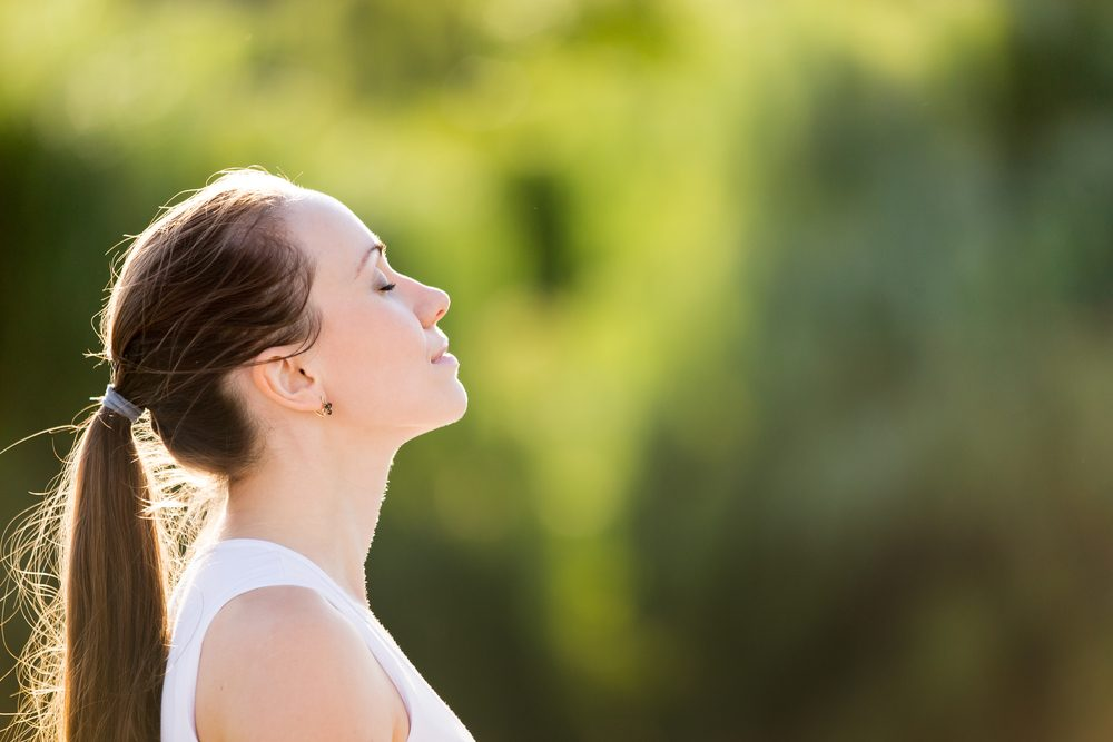 Young woman, breathing deeply, face toward the sun