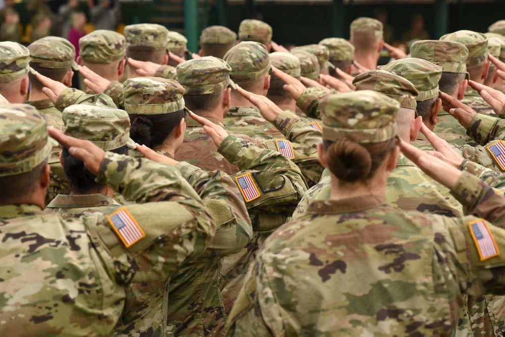 Men and women in fatigues, saluting, backs to the camera