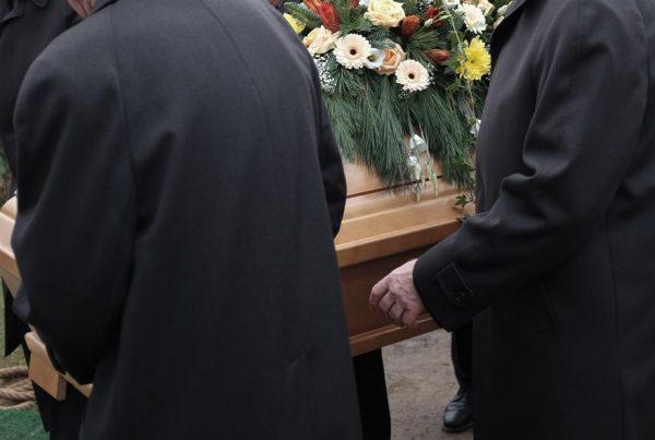 Pallbearers lowering casket into grave