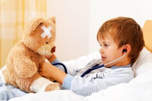 Little boy in bed checking his teddy bear's heartbeat with a stethoscope