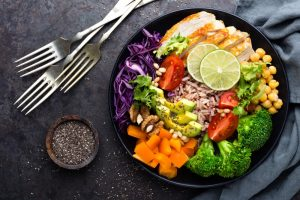 Colorful plate of healthy foods like broccoli, carrots, chicken, tomatoes, brown rice