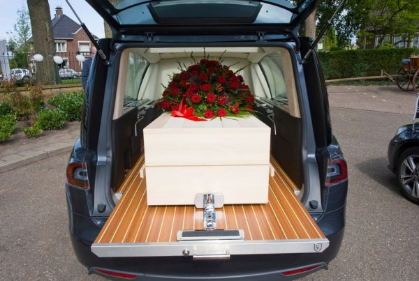 White casket with flower spray of red roses resting in the back of a funeral car