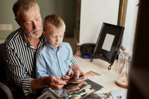 Man holding child on his lap as they look at photographs