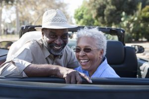 Older couple sitting in a convertible smiling at the camera