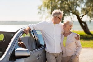 Older couple standing next to car looking lovingly at each other