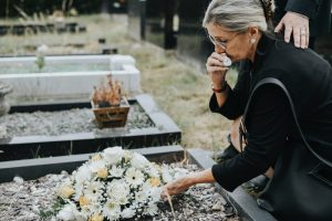 Mature mothing laying wreath on grave