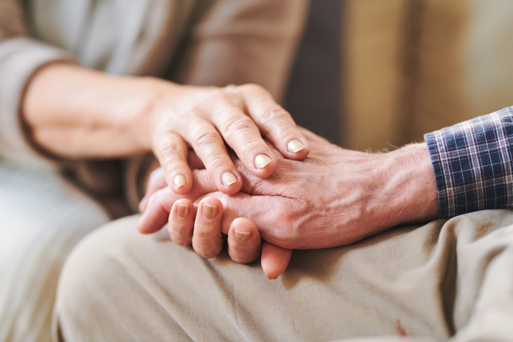 Focus on hands, younger person holding older person's hand in a comforting way