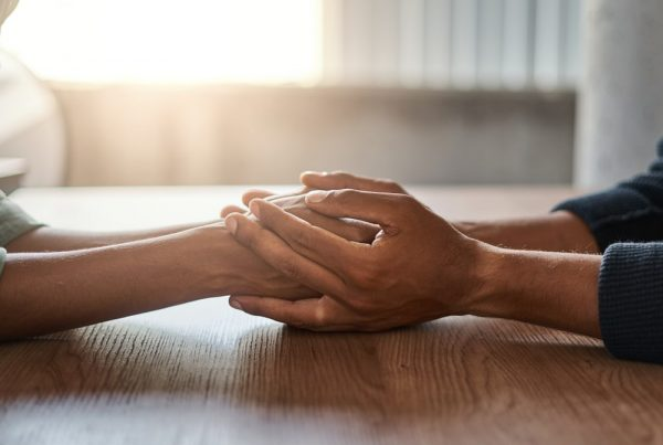 Two people holding hands across table, no faces