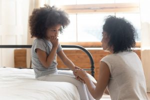 Child sitting on bed with mother kneeling and talking in a loving way