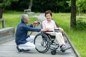 Man crouched beside wheelchair-bound wife, talking and laughing