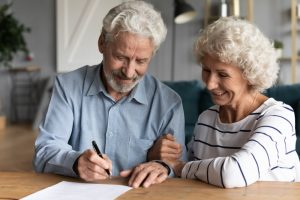 Mature man and wife sitting at table signing documents