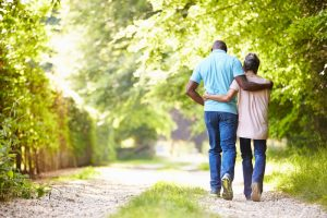 Man and woman walking on a green path outside, arms around each other's waist