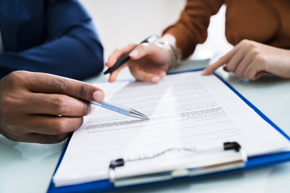 Man and woman reviewing documents on a clipboard
