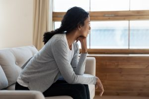 sad woman sitting at home looking out window