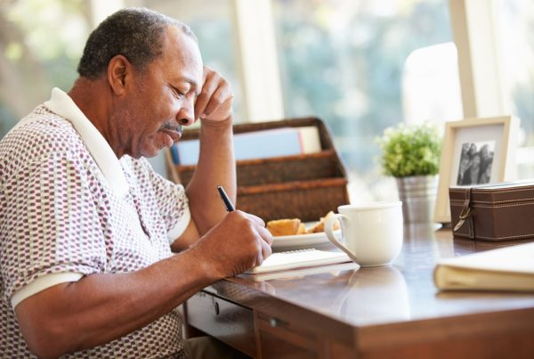 Older man sitting at desk writing letters
