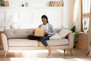 Woman holding box on lap while sitting on couch