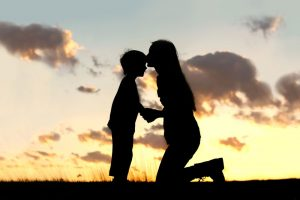 Mother kissing son's forehead at sunset
