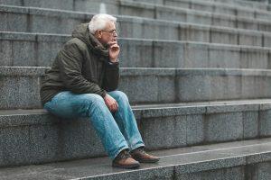 Older man sitting on stone steps thinking