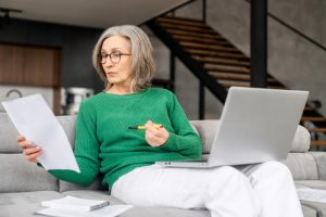 Older woman wearing green sweater sitting on couch doing research