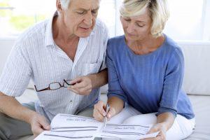 Man wearing white shirt and woman wearing blue shirt reviewing contract