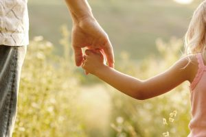 Father holding daughter's hand as they walk outside