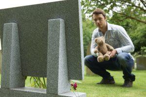 Man laying teddy bear at grave