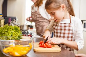 Little girl cutting vegetables in the kitchen with mother