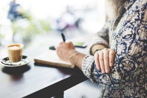 Woman sitting at table, writing on notepad