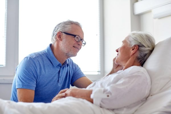 Husband sitting next to wife in hospital bed