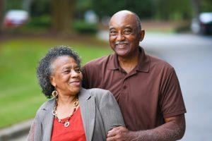 Mature couple walking together, smiling at camera