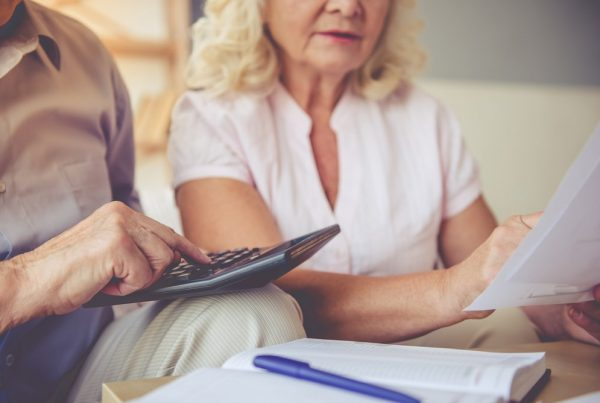 Older man and woman using calculator to add up costs