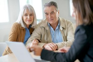 Older man and woman reviewing paperwork with professional