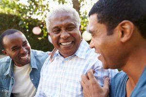 Father with two adult sons laughing and enjoying time together