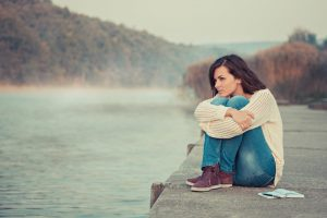 Young woman thinking as she sits beside lake