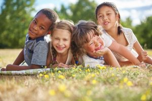 Four children of different ethnic backgrounds smiling while playing outside