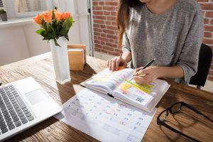 Woman writing on a calendar, outlining her routine for the week