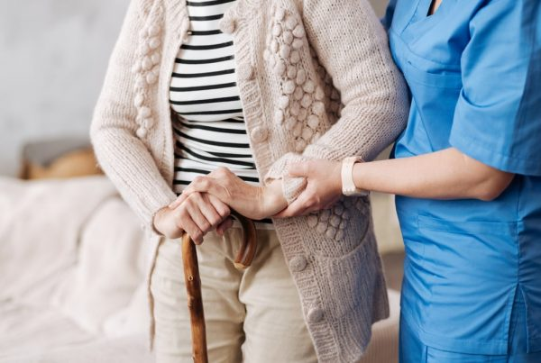 Home health nurse helping woman walk across room