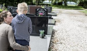 Mother and young son paying respects at a cemetery