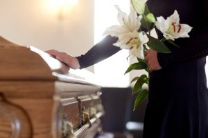 Woman standing next to casket holding white lilies