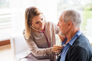 Home health nurse checking older man's heartbeat with stethoscope
