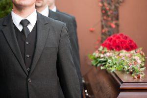 Three men on left side of casket, carrying it