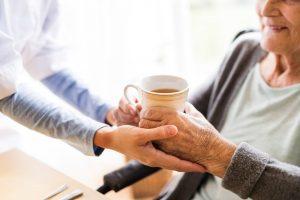 Elderly woman accepting cut of tea from nurse