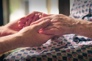 Younger person holding older person's hands in a comforting way
