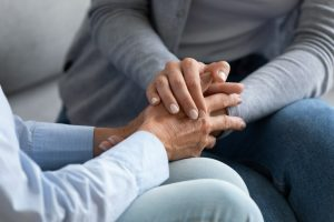 One person holding another person's hands in comfort as they listen