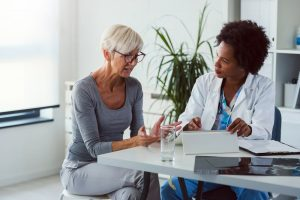Older woman at medical appointment, talking with female doctor who is listening intently