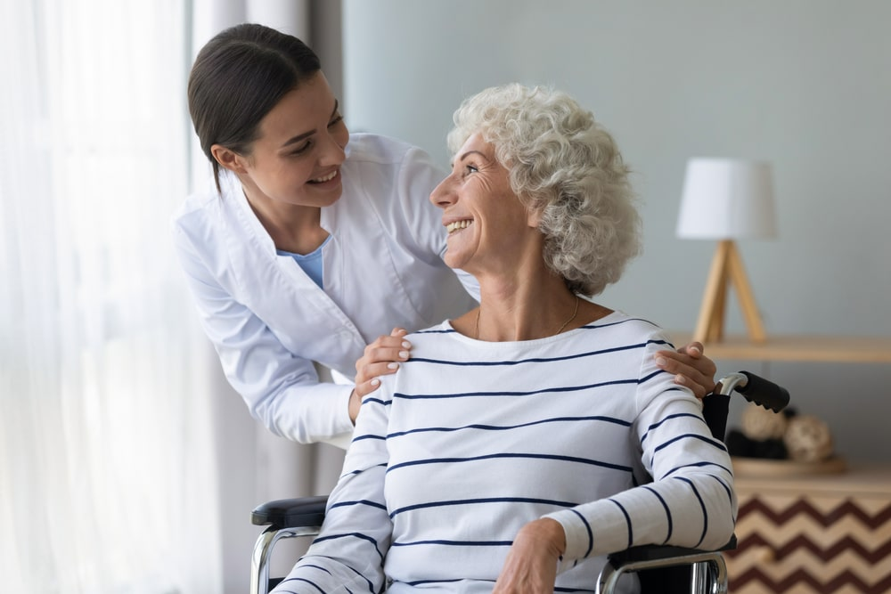 At home aide smiling at and helping elderly female patient
