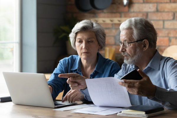 Man and woman sitting at a table reviewing documents, laptop lying on table