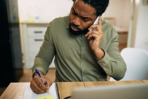 Man on phone asking about insurance, writing down answers